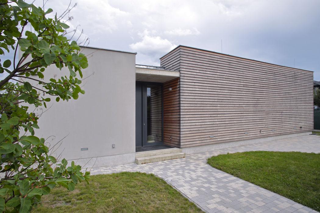 Fasáda směrem doulice je uzavřená, jediné propojení představuje zapuštěné závětří se vstupními dveřmi. Obklad zmodřínových lamel zvýrazňuje horizontální ráz stavby.