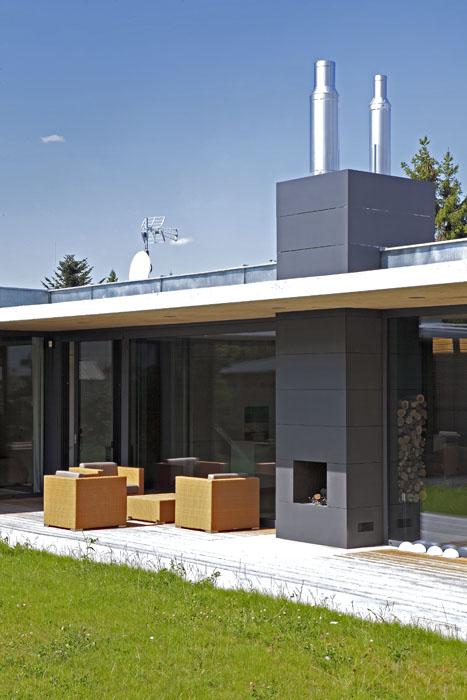 Dominantou exteriéru iinteriéru domu je masivní těleso oboustranného krbu, obložené plechovými šablonami.