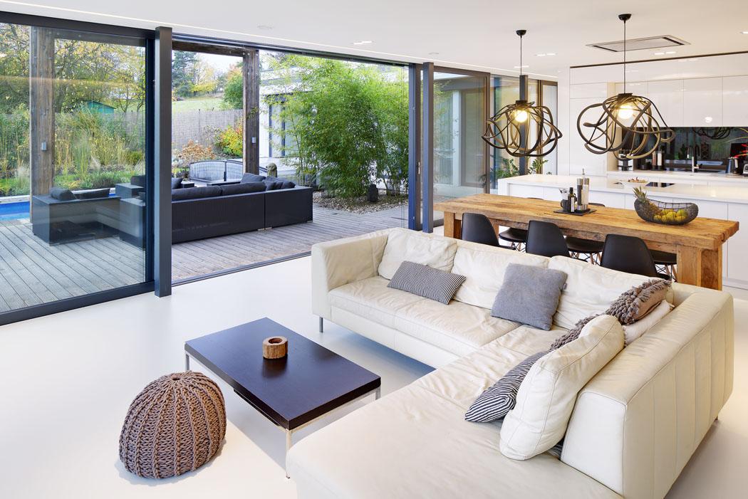 Celý prostor domu opticky zvětšují velké prosklené plochy abílá litá stěrka napodlaze, poznávací znamení domů Ateliéru Kunc Architects.