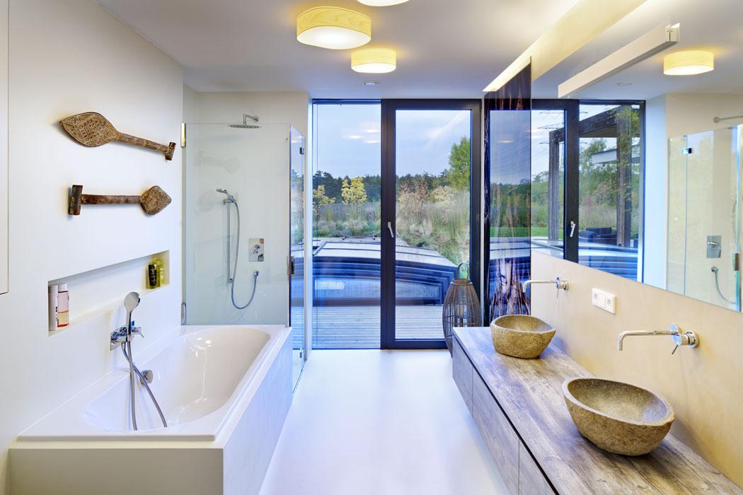 Ivkoupelně architekti mysleli napropojení vnitřního prostoru sexteriérem zahrady. Moderní bílou koupelnu doplňují kamenná umyvadla navozující wellness atmosféru.