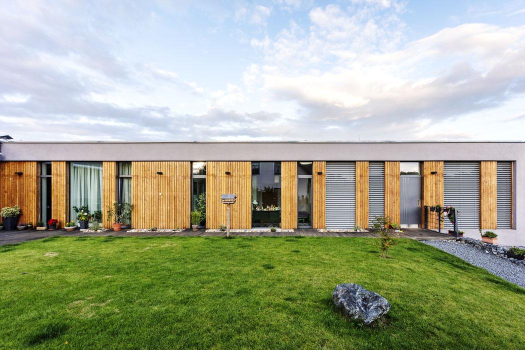 Rytmus prosklených ploch avertikálního dřevěného obkladu, které se střídají všedém obvodovém rámu betonové konstrukce, zajímavě člení aopticky zkracuje protáhlou hmotu stavby.