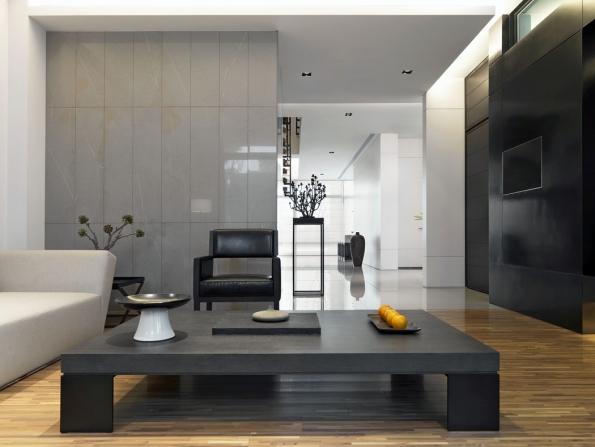 Barevnost minimalistického interiéru je většinou střídmá, vneutrálních tónech. Odstíny šedé oživuje jasná bílá nastropě astěnách spolu sčernými detaily. Zde je černá použitá odvážně nacelou jednu stěnu, aby vyvážila rozlehlý antracitový stolek. Interiér vchladných barvách pocitově prohřívá dřevěná podlaha.