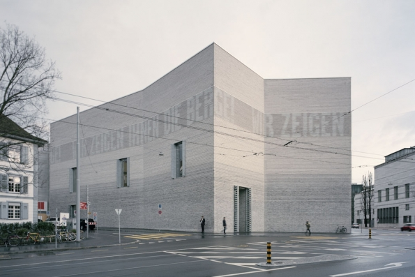 """Brick Awards 2018: Hlavní cena + kategorie Sdílení společného prostoru: Dostavba Muzea umění, Basilej, Švýcarsko Architekt: Christ & Gantenbein, Švýcarsko Nový objekt navazující na historickou budovu používá elementární základní tvary a stavební prvky. Ve fasádě ze světle šedých ražených cihel s plastickými horizontálními drážkami je intergrováno LED osvětlení, které vytváří na fasádě světelné """"nápisy"""" informující o právě probíhajících výstavách."""