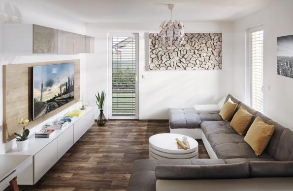 V přízemí se nachází společný obývací prostor ve tvaru L, který je propojen s kuchyní, ale zároveň je od ní příjemně opticky oddělený. Díky několika francouzským oknům je interiér bezprostředně propojený se zahradou.