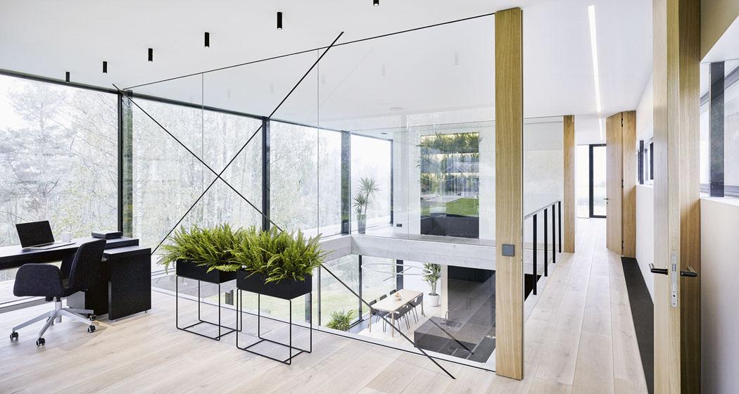 Nejvyšší podlaží má tři stěny ze skla aocelových sloupků aje téměř celé transparentní. Pracovnu dělí odgalerie skleněná stěna, podobně jako protilehlou ložnici.