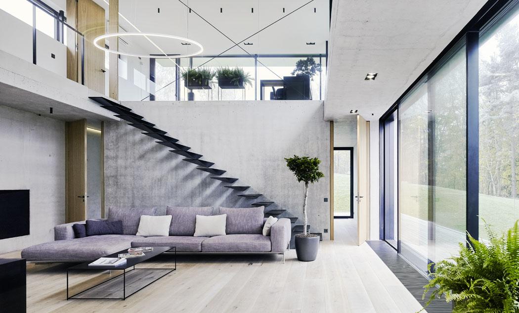 """Ústřední obývací prostor prochází přes dvě podlaží. Celému interiéru dominuje kombinace pohledového betonu, běleného dřeva, skla asolitérů včerné barvě. Schodiště zocelového plechu vetknuté dozdiva působí vzdušně alehce aklame tělem – provedení takového """"majstrštyku"""" je velmi náročné."""