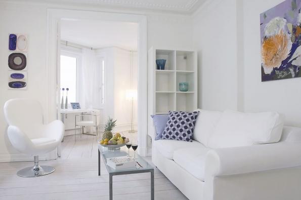 Zde bílý interiér oživují jen dekorace: fialové polštářky, modré skleněné vázy, ovoce namíse apestré obrazy. Celek je velmi svěží amoderní.