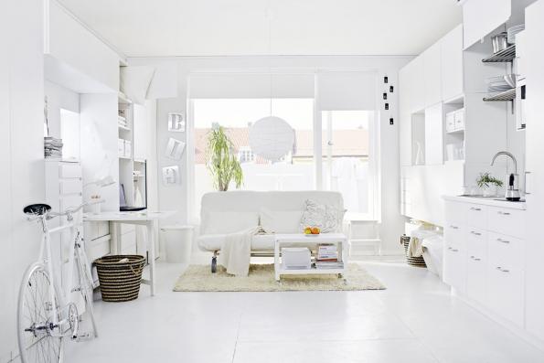 Mezi designéry oblíbený tzv. bílo-bílý interiér decentně oživují jen různé odstíny bílé: odlomené přes teple bílou až pokrémovou. Aprávě mnoha odstínům bílé vděčí interiér jednopokojového bytu zato, že navzdory stěnám důsledně zaplněným úložným nábytkem zůstává velmi vzdušný.