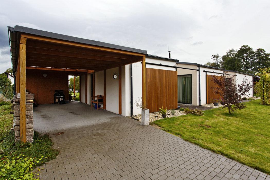 Hlavní vstup dodomu vede přes garážové stání kryté dřevěným přístřeškem. Jeho součástí je imalý sklad zahradního náčiní.