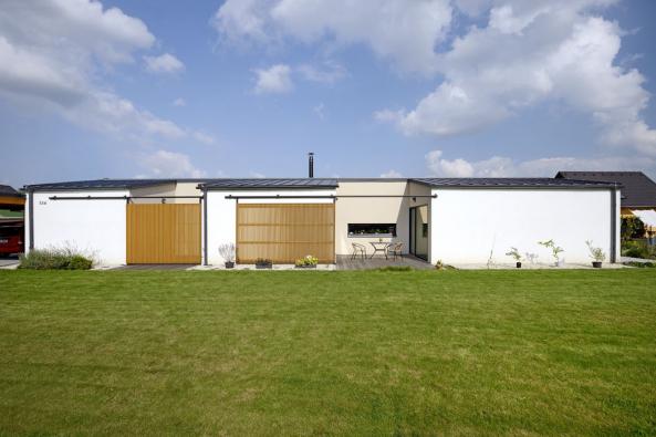 Dřevěné posuvné stěny, zavěšené naocelových kolejnicích, umožňují otevírat azavírat atria zapuštěná dohmoty domu.