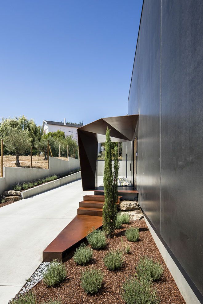 Jednoduchou kompaktní hmotu domu zajímavě oživuje sochařsky tvarované zádveří. Stříška, podesta ivenkovní schodiště jsou vyrobeny zcortenového plechu.