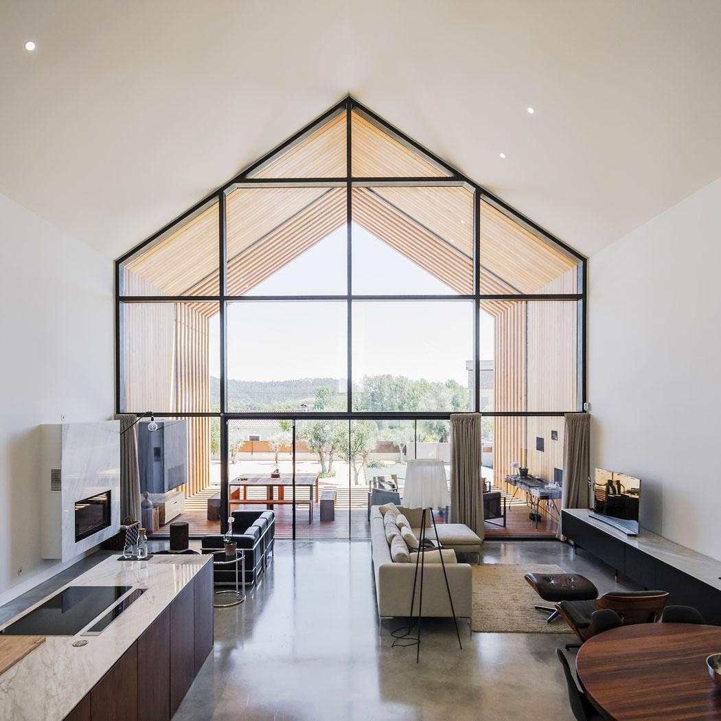 Společná obývací část domu je posuvnými dveřmi propojena sterasou. Také vinteriéru realizoval architekt Saraiva svůj ideál bydlení. Nahladké podlaze zbetonové stěrky vynikne vestavěné vybavení nazakázku zexotického dřeva ivybrané nadčasové solitéry, jako jsou židle akřeslo odCharlese Eamese, funkcionalistická pohovka odLe Corbusiera či stolky odjeho současnice Eileen Grey.