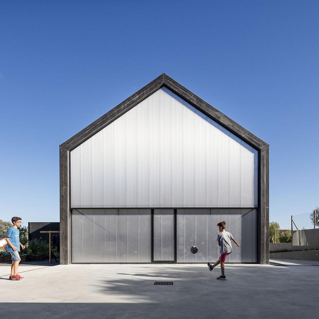 Vseverní části domu je umístěna velkoprostorová garáž. Kryje ji fasáda zocelového plechu svelkoplošnými výsuvnými vraty.