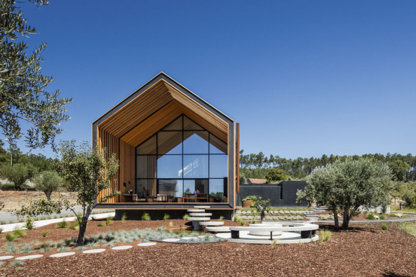 Dům spřiznanou konstrukcí  zmasivních betonových panelů je citlivě zasazen napozemek mezi staré olivovníky. Sterénem jej propojuje atypická sestava betonových prvků. Předsazená terasa zpřírodního dřeva, které kontrastuje skompaktním černým pláštěm domu, prodlužuje azvýrazňuje jeho lapidární hmotu.
