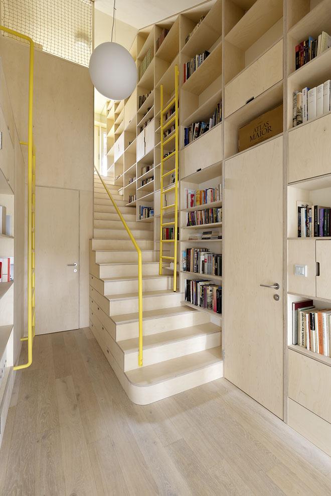 Schodišťová hala je nejen nezbytným komunikačním prostorem, ale současně ivelkou knihovnou. Prostřednictvím vestavného nábytku je účelně propojena se vstupním prostorem.