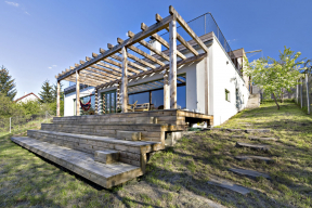 Vilka nenásilně využívá svah vesvůj prospěch. Stupňovitá dřevěná terasa je přirozeným pokračováním vnitřního prostoru domu.
