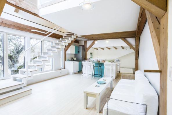 Otevřený interiér využívá denní světlo, zároveň se hlásí kpůvodnímu domu přiznáním dřevěných trámů anosných prvků, které byly zpracovány tradičními tesařskými technikami.