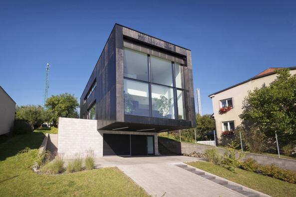 Dvoupodlažní hmota domu získala díky velkému vykonzolování přes suterén lehkost a dynamiku. Fasádní systém s okny se skrytými rámy je tvořen hliníkovými profily o pohledové šířce pouhých 50 mm a umožňuje nerušený výhled (systém FWS 50.SI)