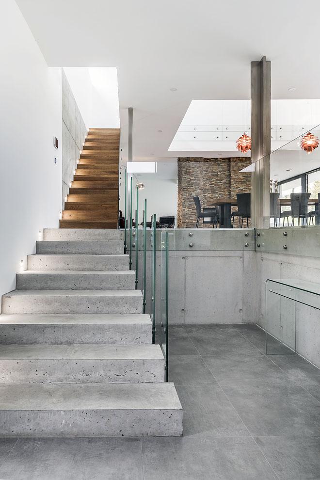 Zádveří tvoří přímou součást společného obývacího prostoru, odděluje jej jen výškový rozdíl 8 stupňů ačiré skleněné zábradlí. Pokračováním této linie je otevřené schodiště dopatra.