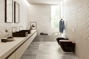 Světlý obklad ve velké místnosti nemusí vypadat fádně. Stěny můžete oživit drobným dekorem nebo plastickými strukturami. Vyniknou v kombinaci  s tmavým nábytkem či tmavou sanitární keramikou. Na fotografii je obklad série Medley Sand (vyrábí Ceramica Supergres)