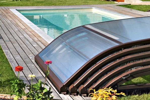 Nízké posuvné zastřešení z práškově lakovaných hliníkových profilů a polykarbonátových panelů, odolných proti UV záření. Počet dílů podmiňuje délka bazénu (DESJOYAUX)