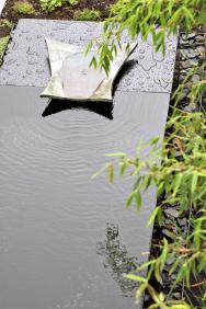 Namaličkou stometrovou zahrádku vOlomouci navrhl atelier Flera vodní prvek sbronzovým detailem. Původní návrh nátoku byl tvaru rejnoka, jehož podoba se pomaličku zjednodušovala, až sochař Michal Trpák přišel stakto krásnou ačistou formou