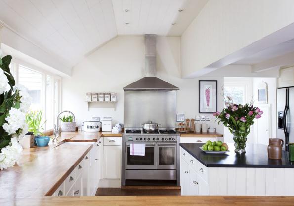 Typická venkovská kuchyně působí mile, čistě aútulně. Osvědčenou symbiózu bílého laku spřírodním dřevem doplňují drobné dekorace, mísa sovocem aživé květy.