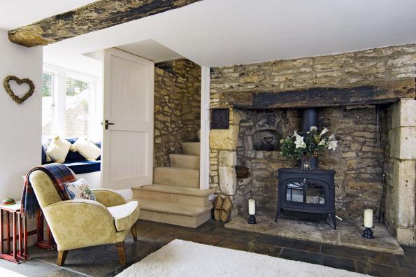 """Ukázka dokonalé harmonie tradičních materiálů: kamenná dlažba barevně krásně ladí se štípanými kameny zdiva, pískovcovými schody ioprýskaným dřevem stropního trámu. Čistě bílá malba stejně jako bíle natřené dveře interiér """"ztěžklý"""" kamenem příjemně prosvětluje aodlehčuje."""