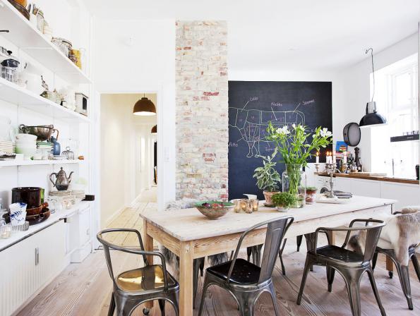 Této kuchyni vévodí přírodní materiály: dřevo, kov arežné cihly vytvářejí působivé popředí velkorysé tabuli, která vinteriéru funguje jako přirozený vizuální magnet.