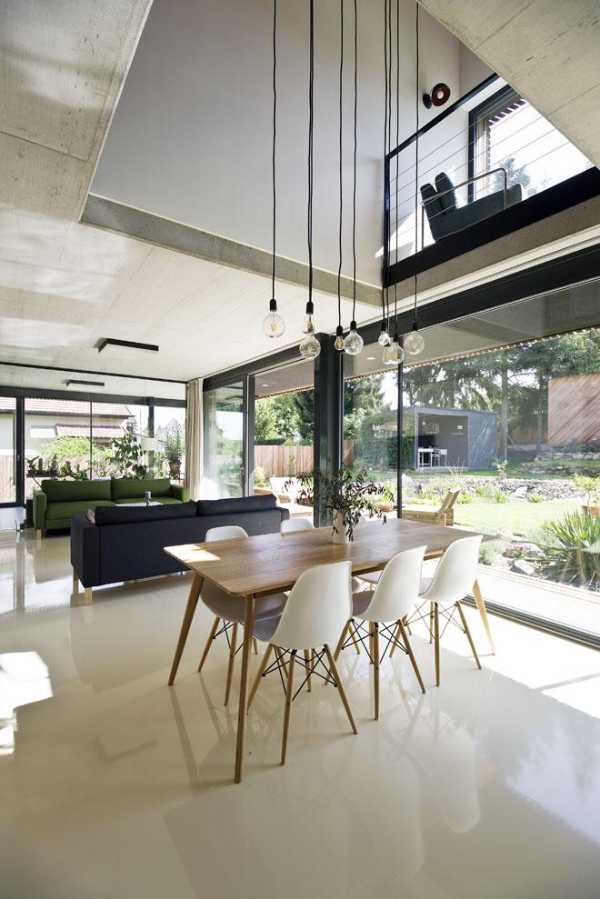 Zahrada vstupující plně prosklenými stěnami do společné obývací části má v domě hlavní slovo. Vybavení interiéru je čistě funkční a jednoduché, podlaha z hladké bílé stěrky tvoří protiváhu surové struktury betonového stropu.