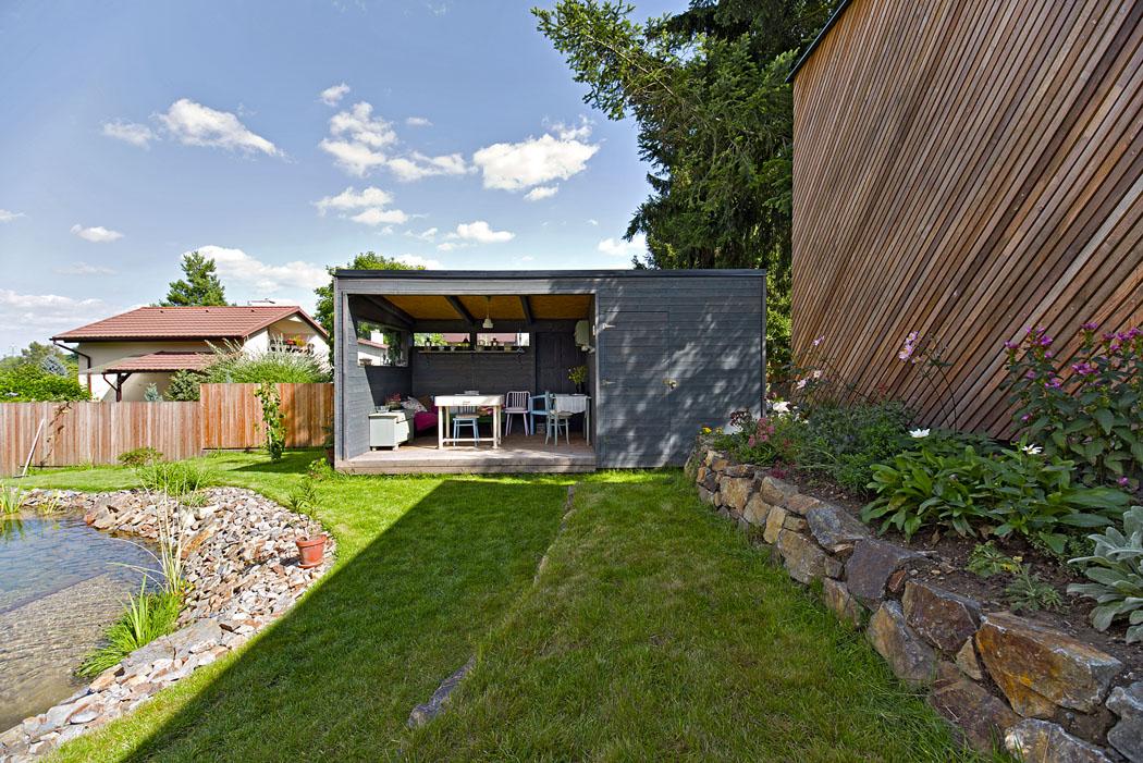 Z obývacího prostoru je přes zahradu vidět do zčásti prosklené garáže a do zahradního domečku s venkovní kuchyní a saunou.