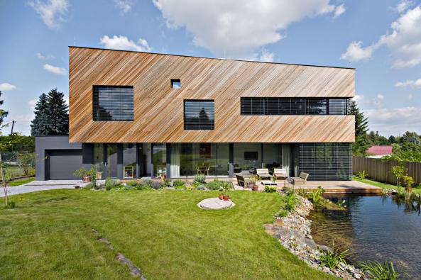 Přízemí ve skle, patro ve dřevě – to je základní výtvarný koncept fasád. Šikmo orientovaný dřevěný obklad dává stavbě jednoduchého tvaru výrazný dynamický vzhled.