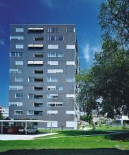 Bytový dům ve Švýcarsku, zateplený fasádním systémem Sto, kombinuje na fasádě přírodní kámen, keramický obklad a skleněnou mozaiku.