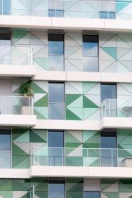 Bytový dům ve Francii s fasádou, kombinující kontaktní zateplovací systém StoTherm Classic, předsazený provětrávaný zateplovací systém StoVentec Glass, složený ze skleněných panelů různých tvarů a bílý fasádní povrch StoSignature.
