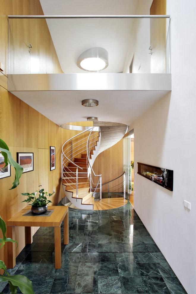 Pohled dohaly stočitým schodištěm anerezovým zábradlím. Stěny izakončení haly jsou obloženy dubovými panely, dominantní jsou i velké kruhové světlíky.