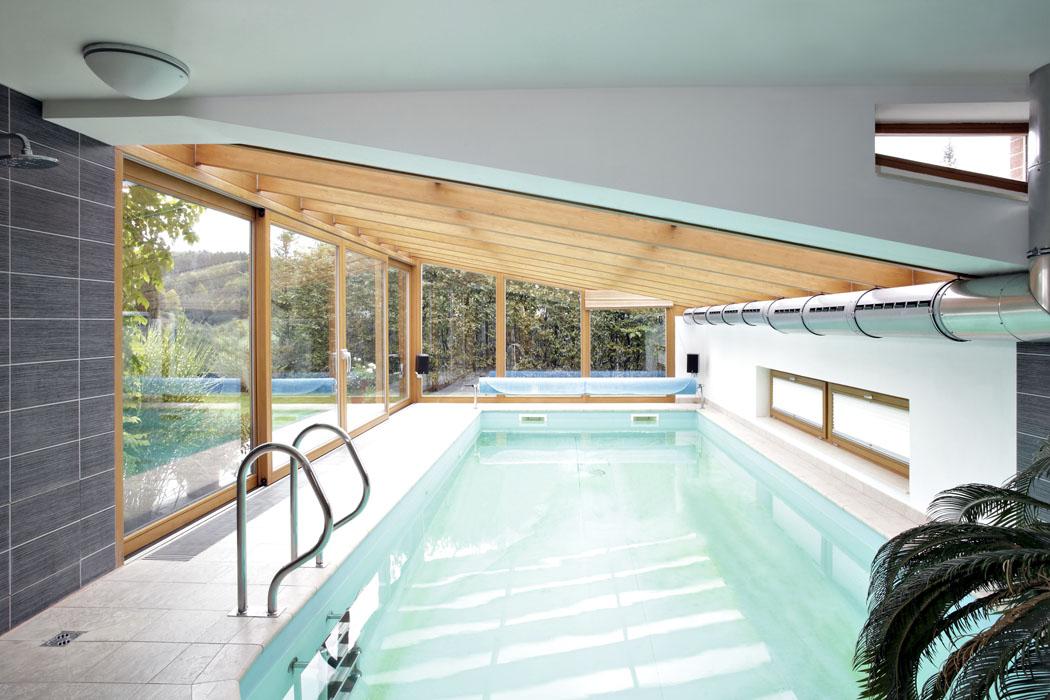 Vnitřní bazén, který vystupuje zhmoty domu, je přístupný zkuchyně/jídelny. Vteplém období je možné otevřít velké dvoudílné dveře apropojit bazén se zahradou.