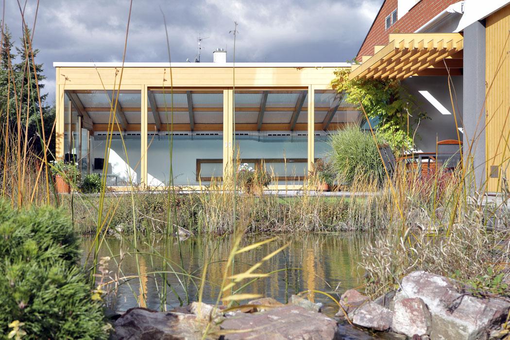 Bazén vystupuje zinteriéru domu do profesionálně vytvořené zahrady spřírodním jezírkem.