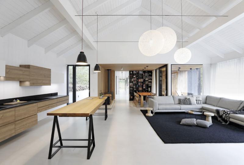 Interiér společného obývacího prostoru je otevřen dokrovu avymezen plochami bílých stěn, hladkých stěrkových podlah abíle natřeného dřeva. Doplňují je přírodní dřevo aakcenty černé ašedé barvy. Architekti tak jednoduše vystihli esenci skandinávského stylu.