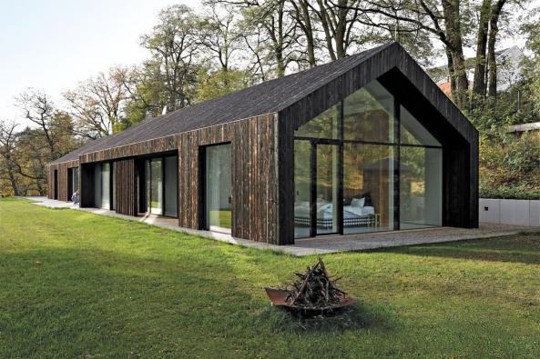 Pohled naložnicovou část domu. Dozákladní hmoty tradičního tvaru jsou zapuštěny prosklené plochy nacelou výšku. Tento koncept vytváří odlehčení, plasticitu  azajišťuje potřebné venkovní stínění.