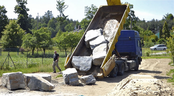 """Dovoz velkých kamenů napozemek je vždy nesnadný, zde se vzpříčily při vysypávání. Každý z""""kousků"""" má 3–5 tun. Přesto je kontejner velmi dobré řešení, má nízké bočnice aje dlouhý, takže se kameny nenakládají vlomu zvelké výšky anasebe. Při vykládání si konec kontejneru řidič pustí až kzemi apopojíždí – tím eliminuje rozbití kamenů jeden odruhý."""