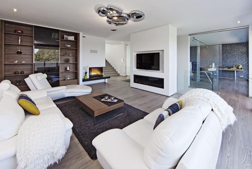 Společná obývací část vpřízemí je jeden velký prostor, členěný dílčími předěly – schodišťovou stěnou, prosklenými dveřmi apod.  Tím jsou zajištěny volné průhledy napříč domem.