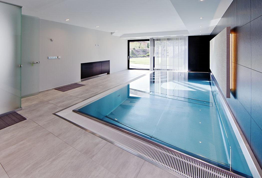 Bazén zaujímá zhruba čtvrtinu přízemí domu a v létě jej lze pomocí posuvné prosklené plochy přímo otevřít do zahrady.
