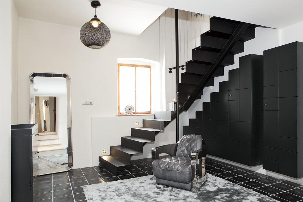 Chodba, původní čedičová dlažba, ocelové schodiště slankovým zábradlím, nábytek vmatně černém laku navržen namíru kopírující tvar schodiště, lustr Non Random Light, Moooi, zrcadlo Deja Vu, Magix