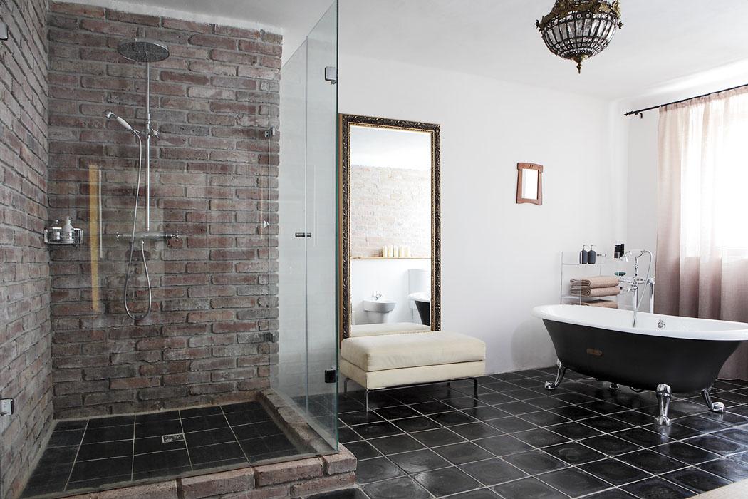 Koupelna vpřízemí, zrcadla aosvětlení popůvodním majiteli, čedičová dlažba také původní, atypický sprchový kout byl řešen zakázkovou výrobou, dobová solitérní vana abaterie