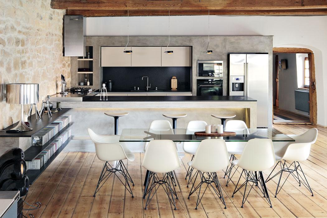 Kuchyně sjídelním koutem, jídelní židle Vitra – Eames Plastic Side Chair, design Charles & Ray Eames, stůl odMagis – Baguette, design Ronan & Erwan Bourellec, kuchyně zasazená vbetonové stěně, dvě úrovně pracovní plochy, pracovní deska zpřírodního kamene – žula Nero Assoluto, deska uvarného centra znerezu, závěsná svítidla nadostrůvkem odznačky Occhio – Sento