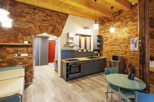 Loftový cihlový apartmán pro celou rodinu je rovněž vybaven originálním trubkovým nábytkem. Kombinace dřeva, kovu acihel je velmi příjemná.