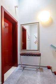 Vstupní chodba doapartmánu UP vybavená dobovými solitérními doplňky – zrcadlem aúzkým trubkovým odkládacím stolkem.