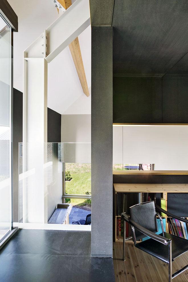 """Vcelém interiéru architekt dbal naotevřené průhledy. Zhorního podlaží je vidět dolů přes schodiště ataké """"oknem"""" vknihovně.."""