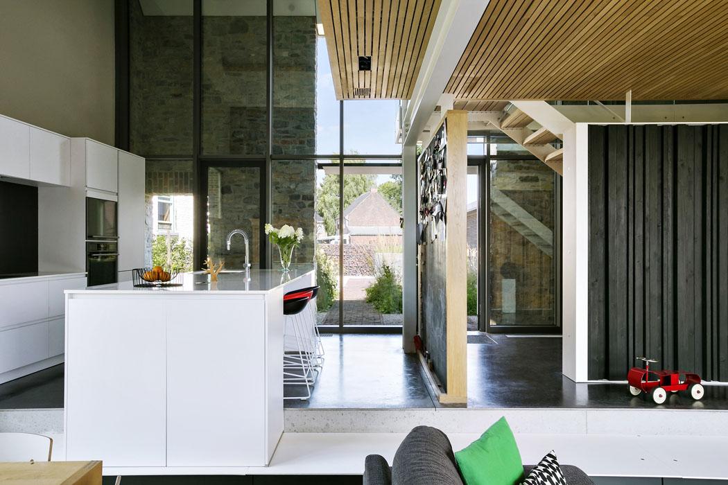 Vstupní hala se schodištěm je přímo průchozí dospolečného obývacího prostoru. Vymezují ji pouze příčky, obložené dýhovanými deskami adřevěnými profily. Vkuchyni slouží příčka jako magnetická tabule.
