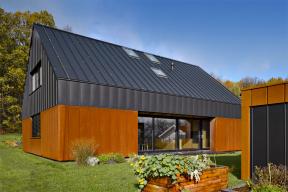Kompaktní fasáda jednoduchého domu je členěna vertikálními falcovanými spoji cortenového a černého plechu. Barevný kontrast doplňují prosklené plochy.